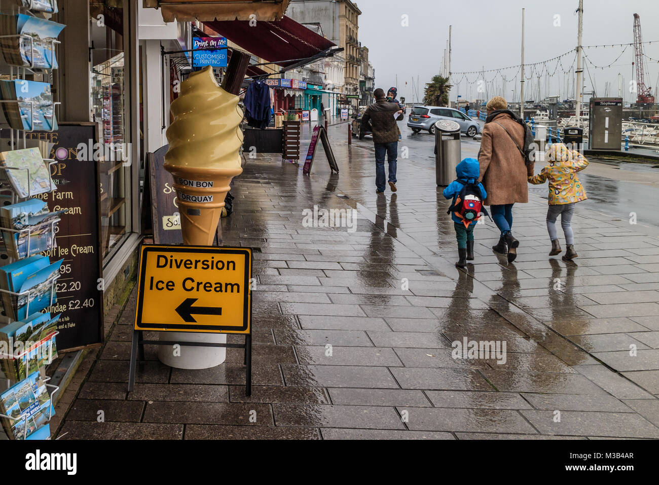 Woman with two children walking along Torquay seafront in wet weather at the start of the February 2018 half term - Stock Image