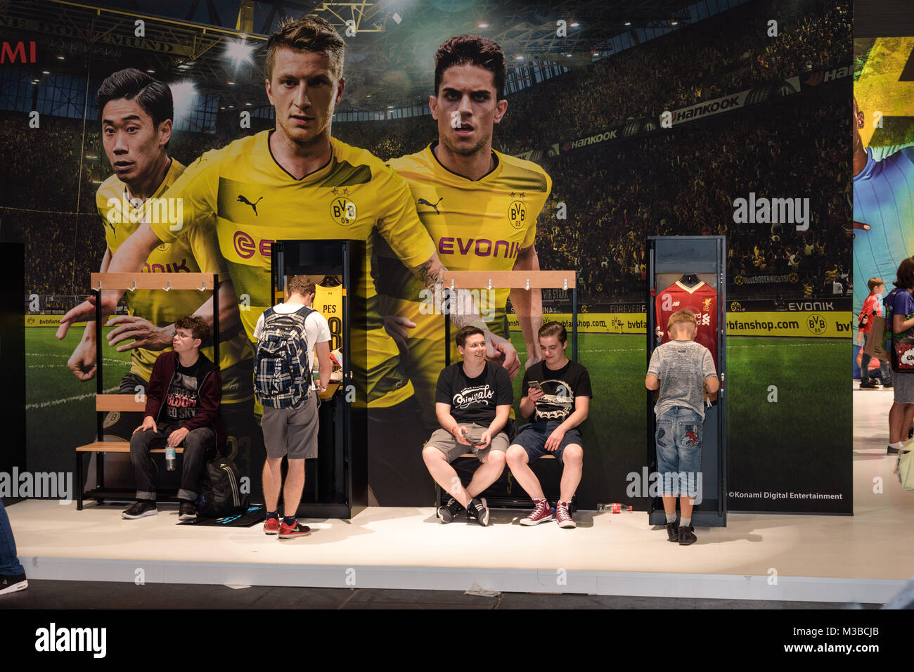 Cologne, Germany - August 24, 2017: Boys stand and sit in front of a BVB advertisement for Pro Evolution Soccer - Stock Image