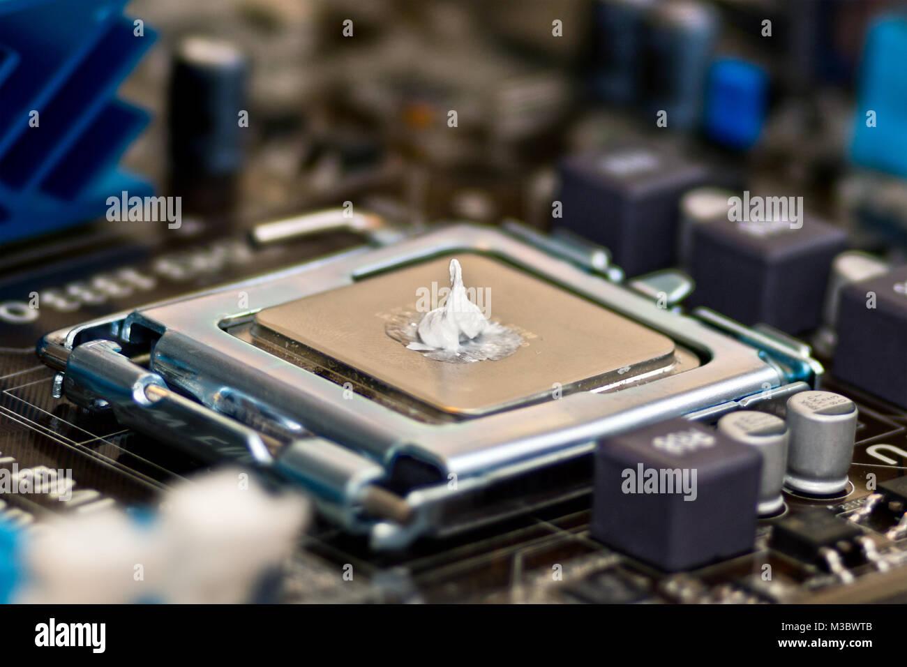 Geschlossener LGA775 CPU Sockel (Land Grid Array) mit eingelegter CPU und Tropfen Wärmeleitpaste, Prozessorsockel Stock Photo