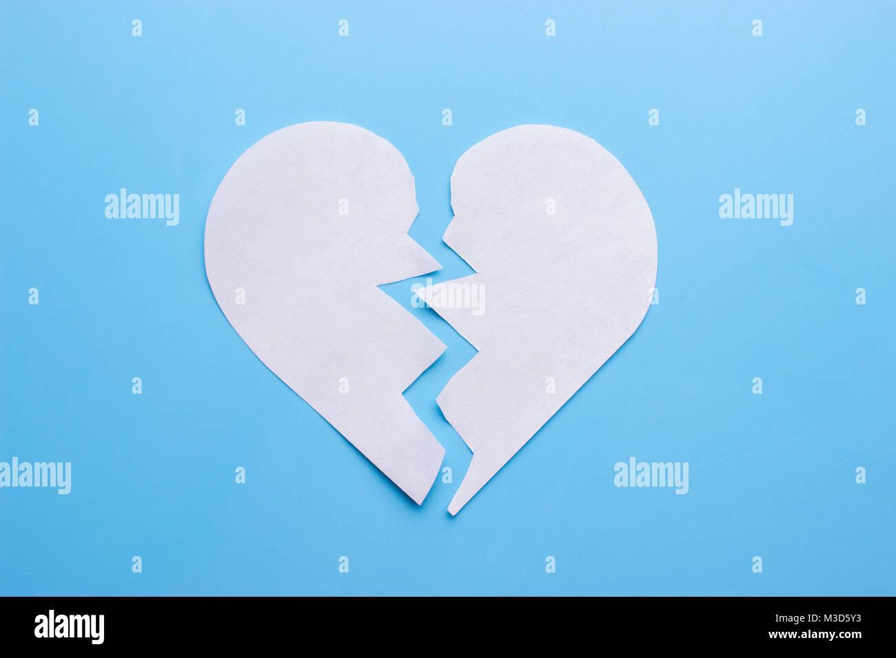 Broken heart on blue background. breakup concept - Stock Image