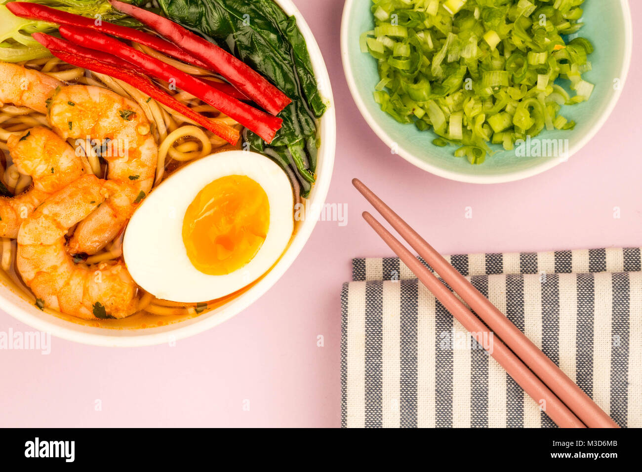 Japanese Style Prawn And Noodle Ramen Soup With Pak Choi And Chillies Against A Pink Background - Stock Image