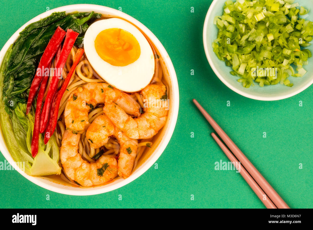 Japanese Style Prawn And Noodle Ramen Soup With Pak Choi And Chillies Against A Green Background - Stock Image