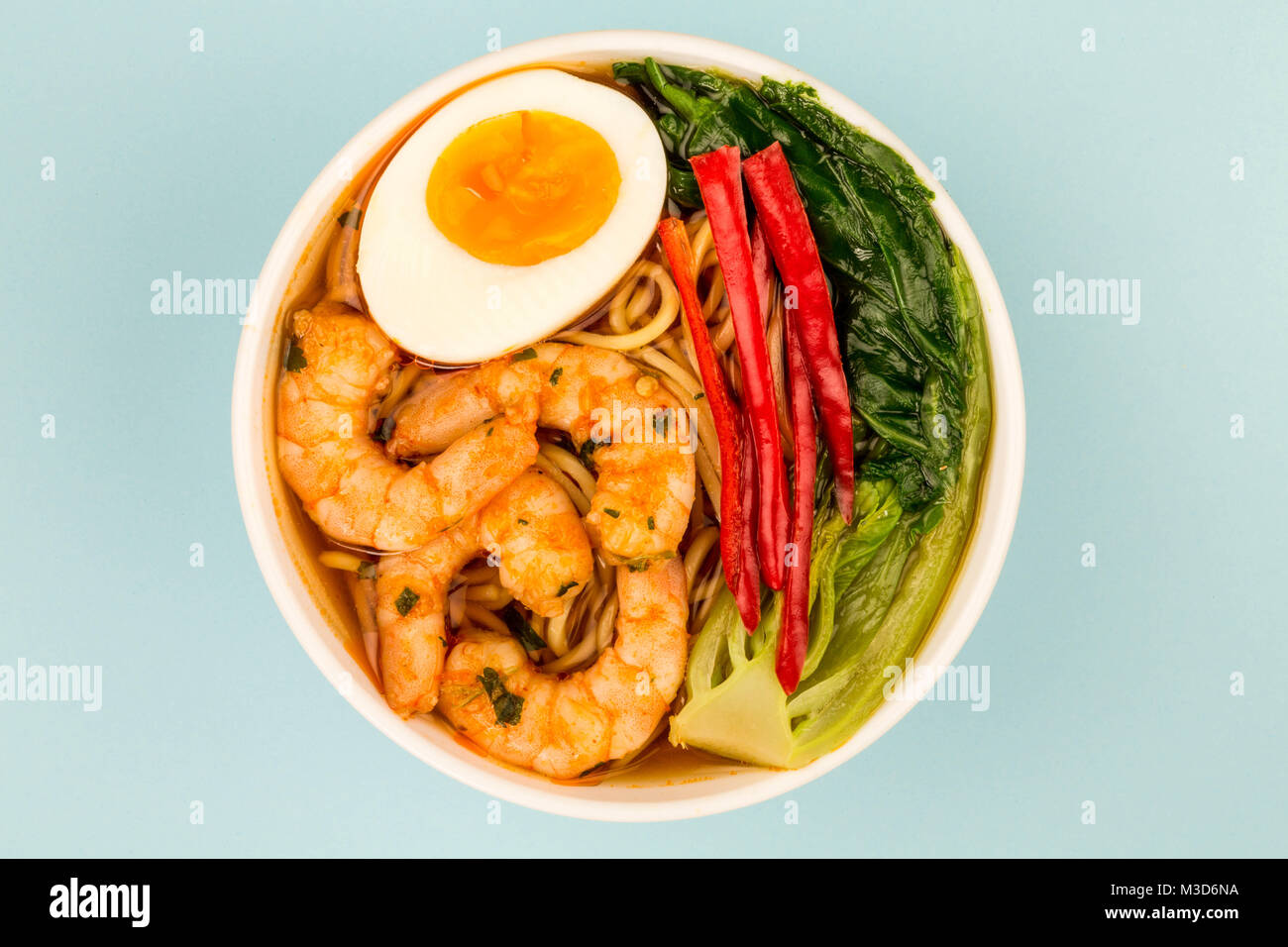 Japanese Style Prawn And Noodle Ramen Soup With Pak Choi And Chillies Against A Light Blue Background - Stock Image