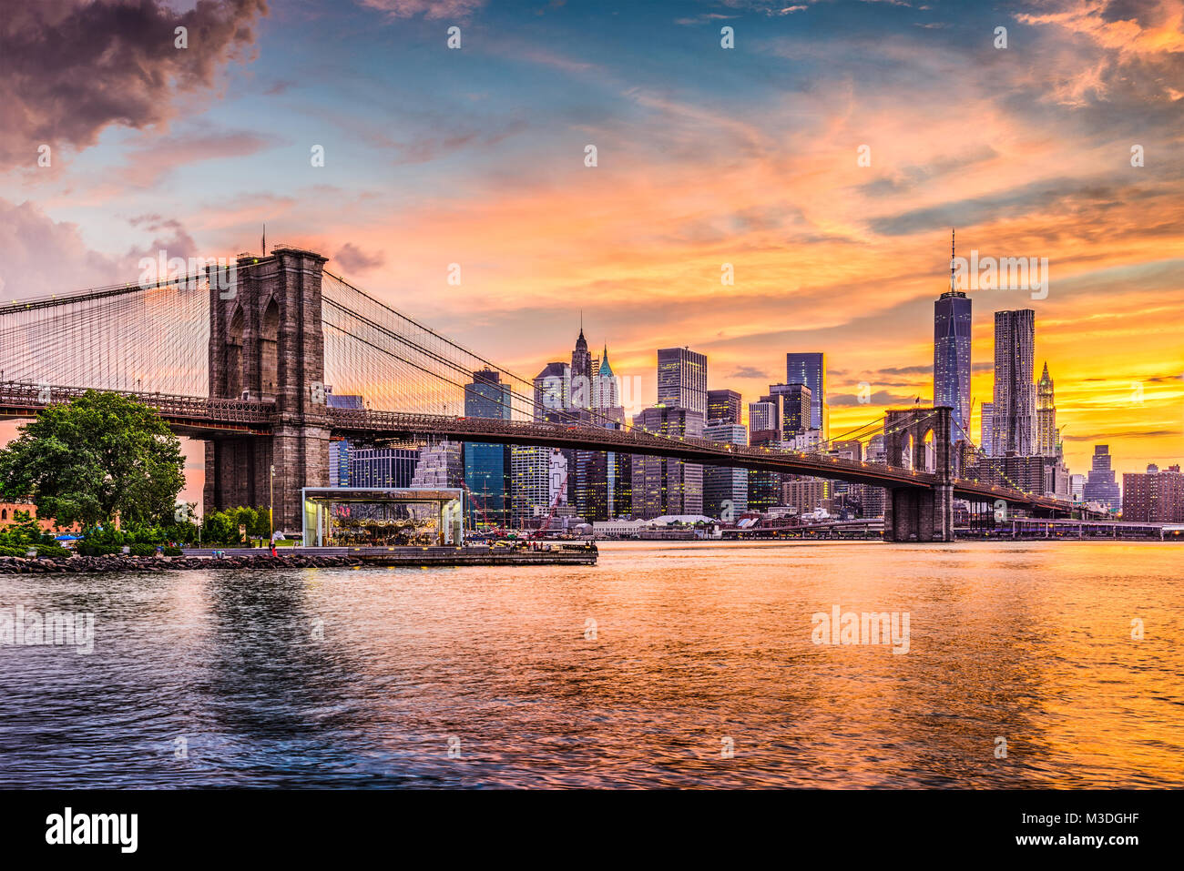 New York City Skyline on the East River with Brooklyn Bridge at sunset. - Stock Image