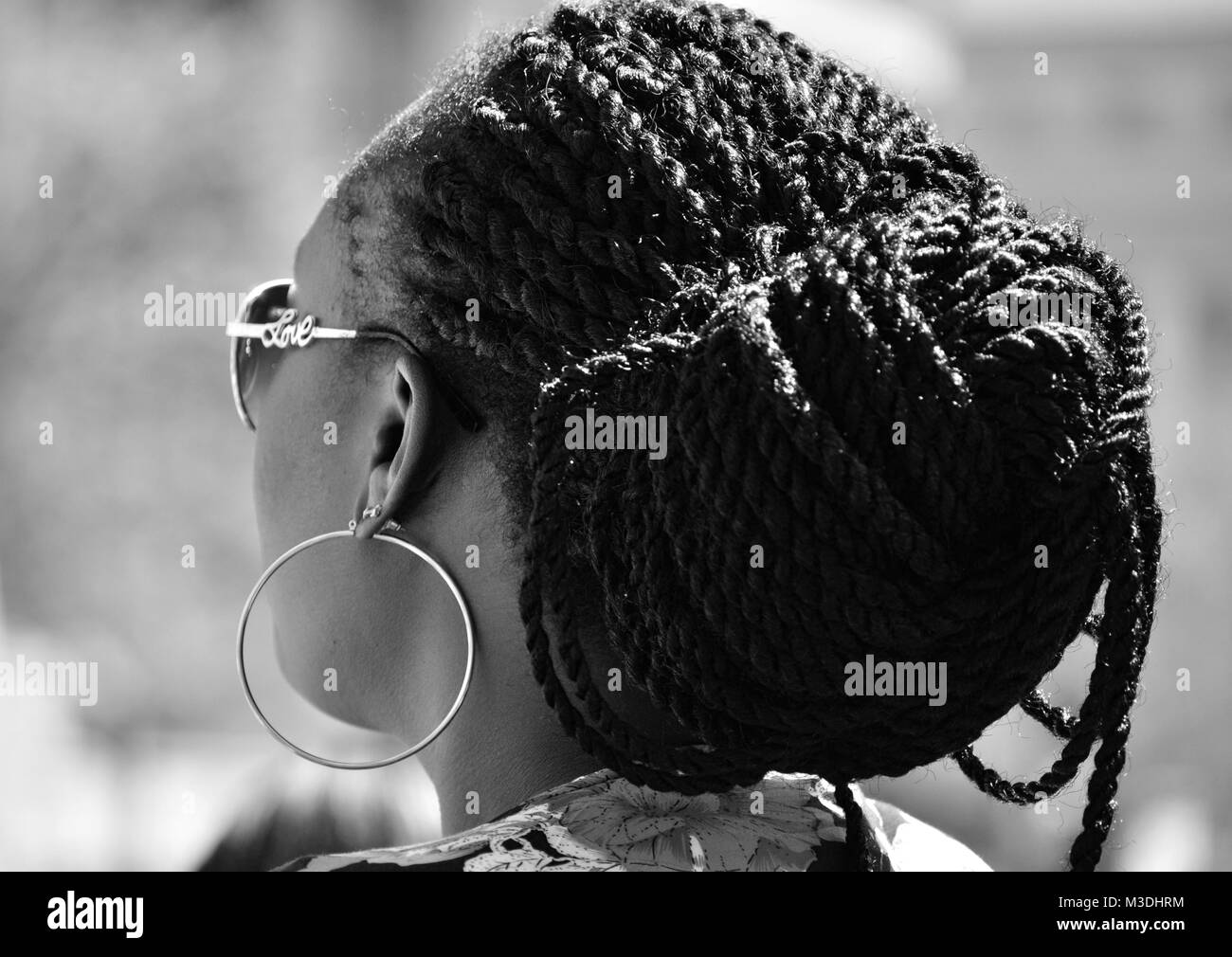 Black and White side profile of African American woman with braids and big ear rings - Stock Image