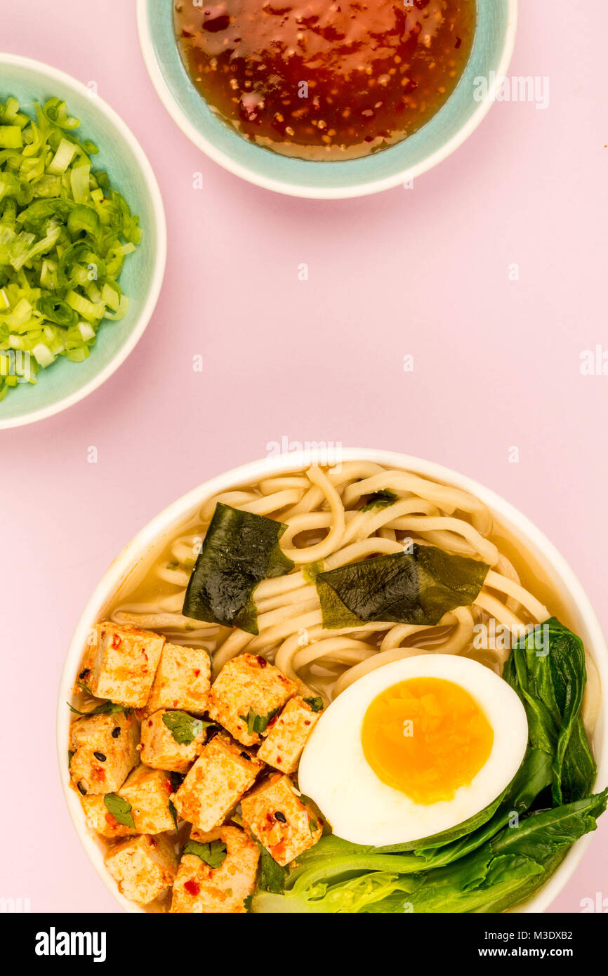 Japanese Style Vegetarian Tofu Noodle Ramen Soup or Broth Against A Pale Pink Background - Stock Image
