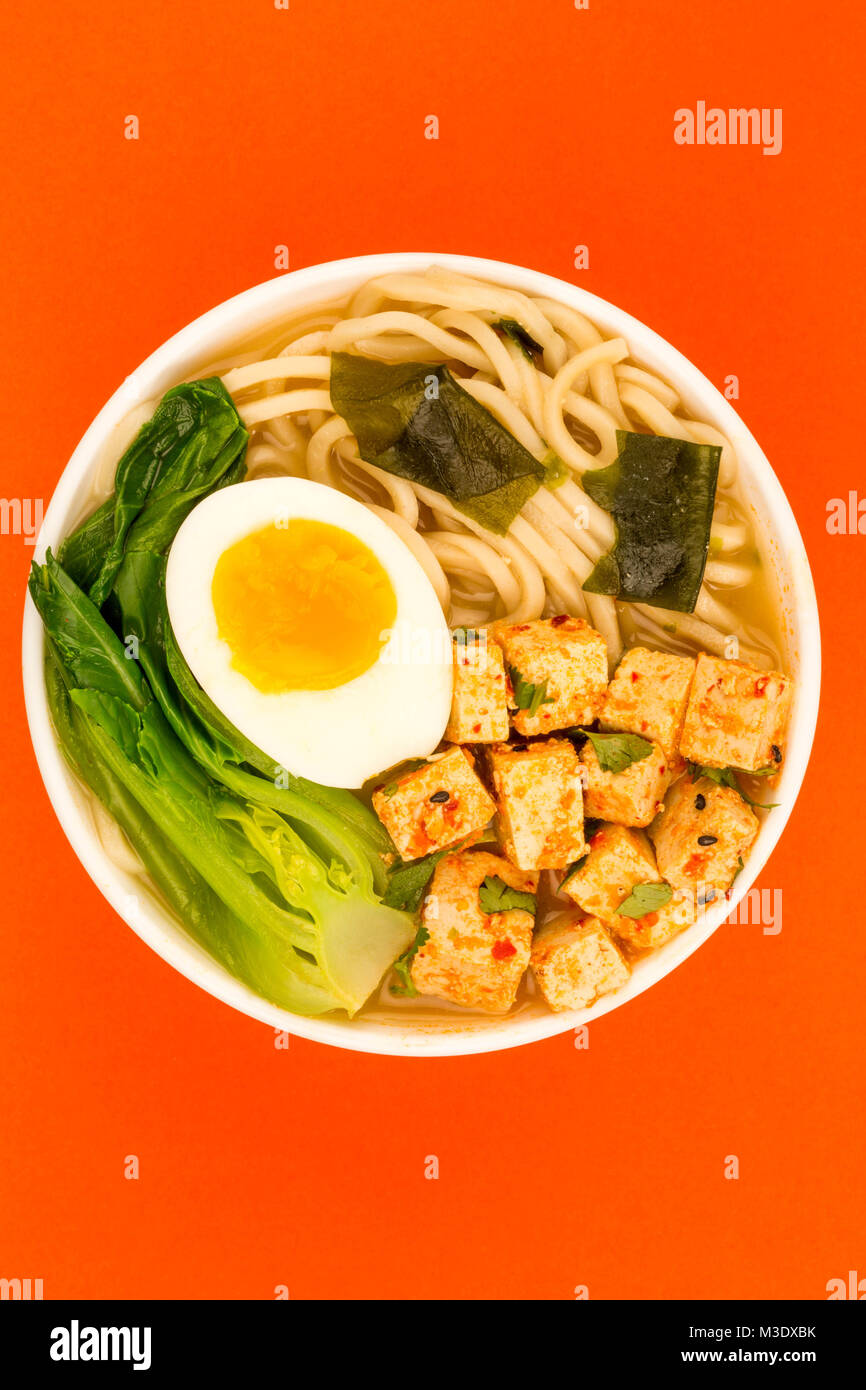 Japanese Style Vegetarian Tofu Noodle Ramen Soup or Broth Against A Red Background - Stock Image