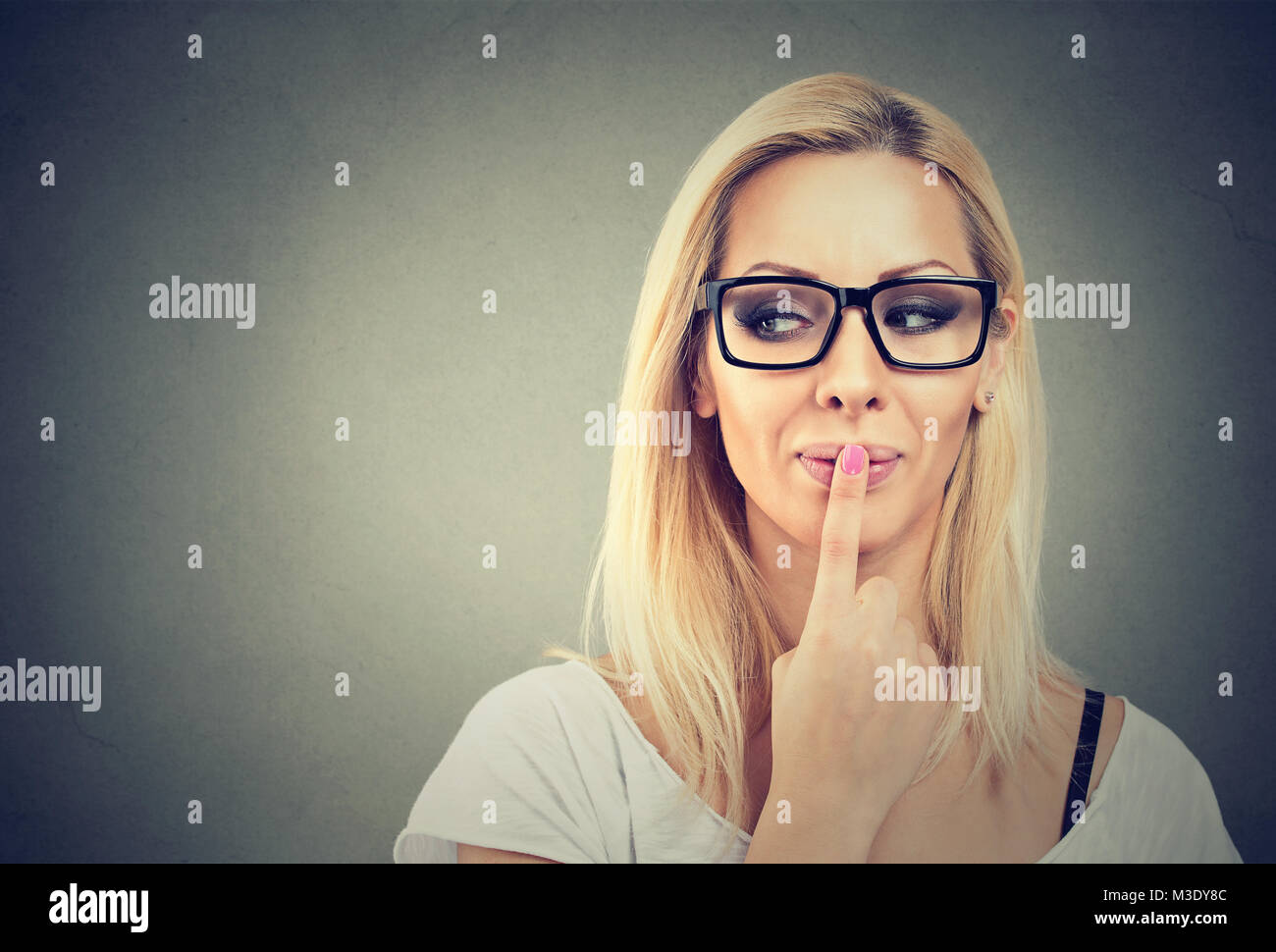 Young flirty model in eyeglasses touching lips looking away on gray. - Stock Image