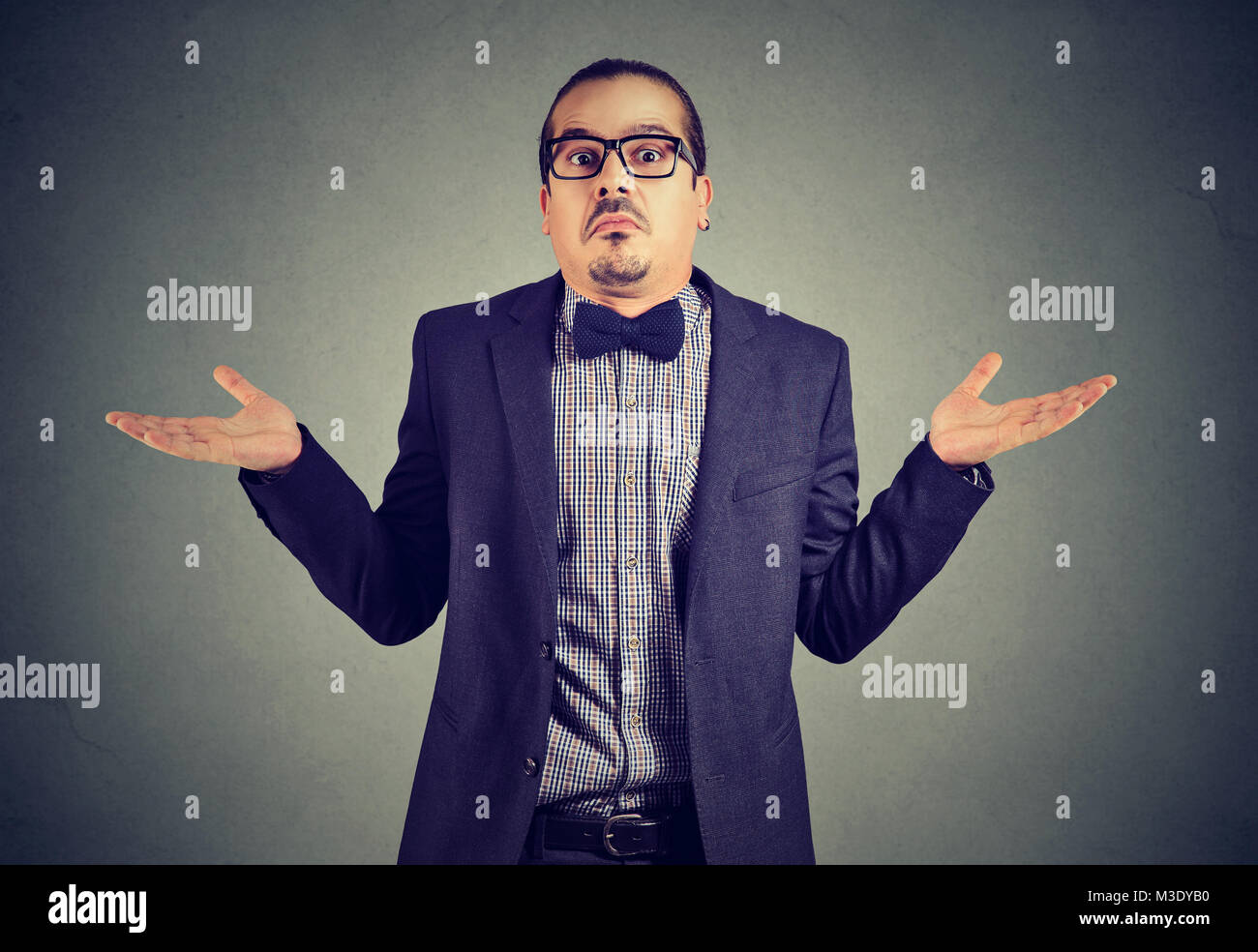 Young man in formal clothing shrugging shoulders while posing on gray and looking confused. - Stock Image