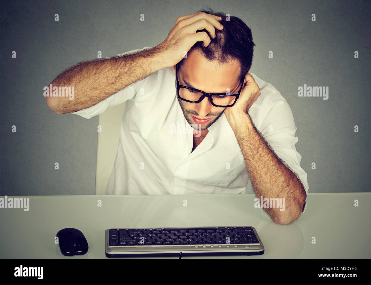 Formal man in eyeglasses scratching head trying to remember password looking at keyboard. - Stock Image