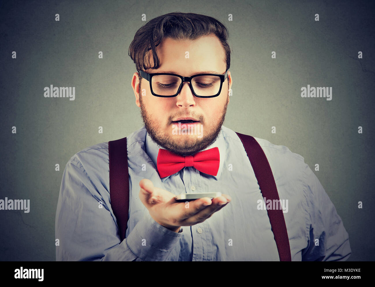 Chubby man holding smartphone and having AI conversation talking aloud. - Stock Image