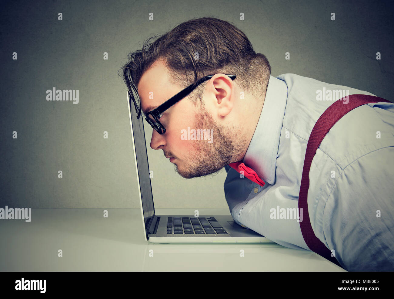 Side view of chunky man with bad vision having sedentary way of work and looking unmotivated. - Stock Image