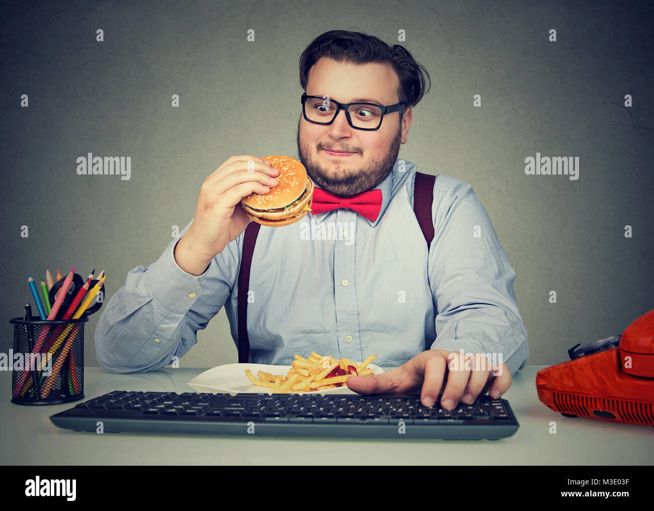 Obese man in glasses eating fast food while working in office and overeating. - Stock Image
