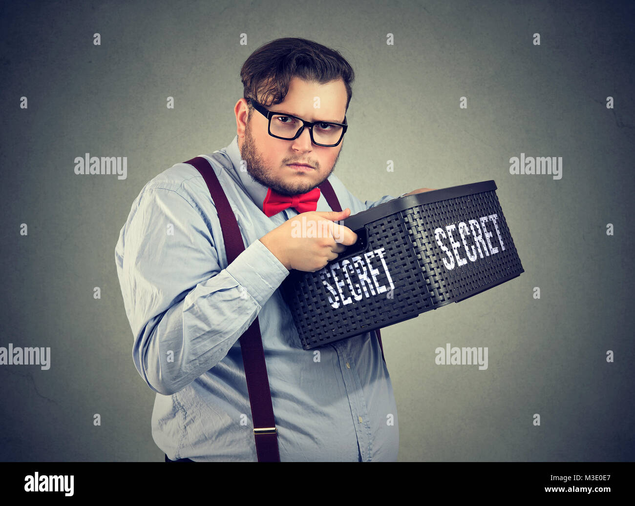Chubby man in eyeglasses hiding secret in box unwilling to share looking suspiciously at camera. - Stock Image