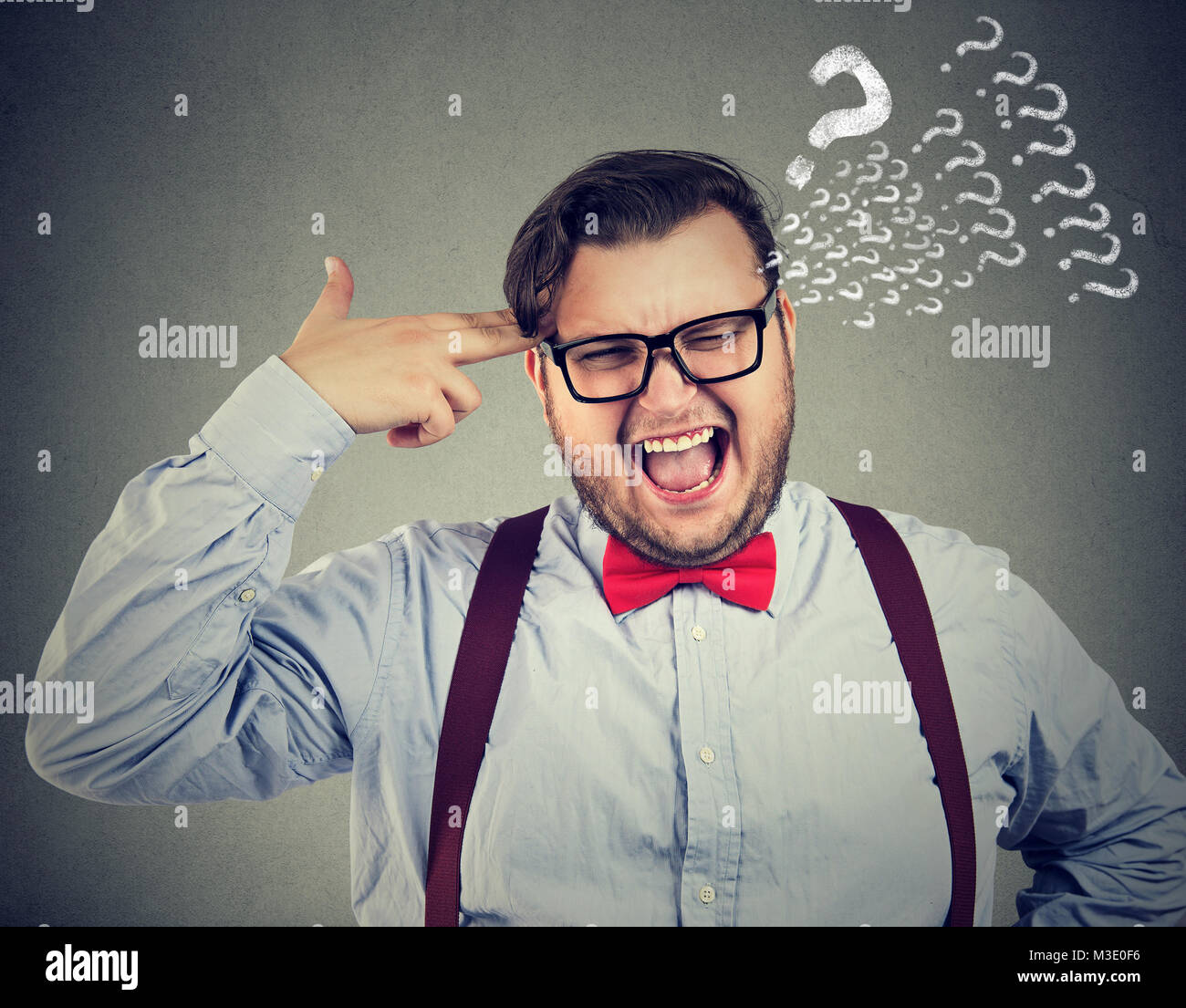 Cheeky man in bow-tie holding fingers to temple looking anxious with questions. - Stock Image