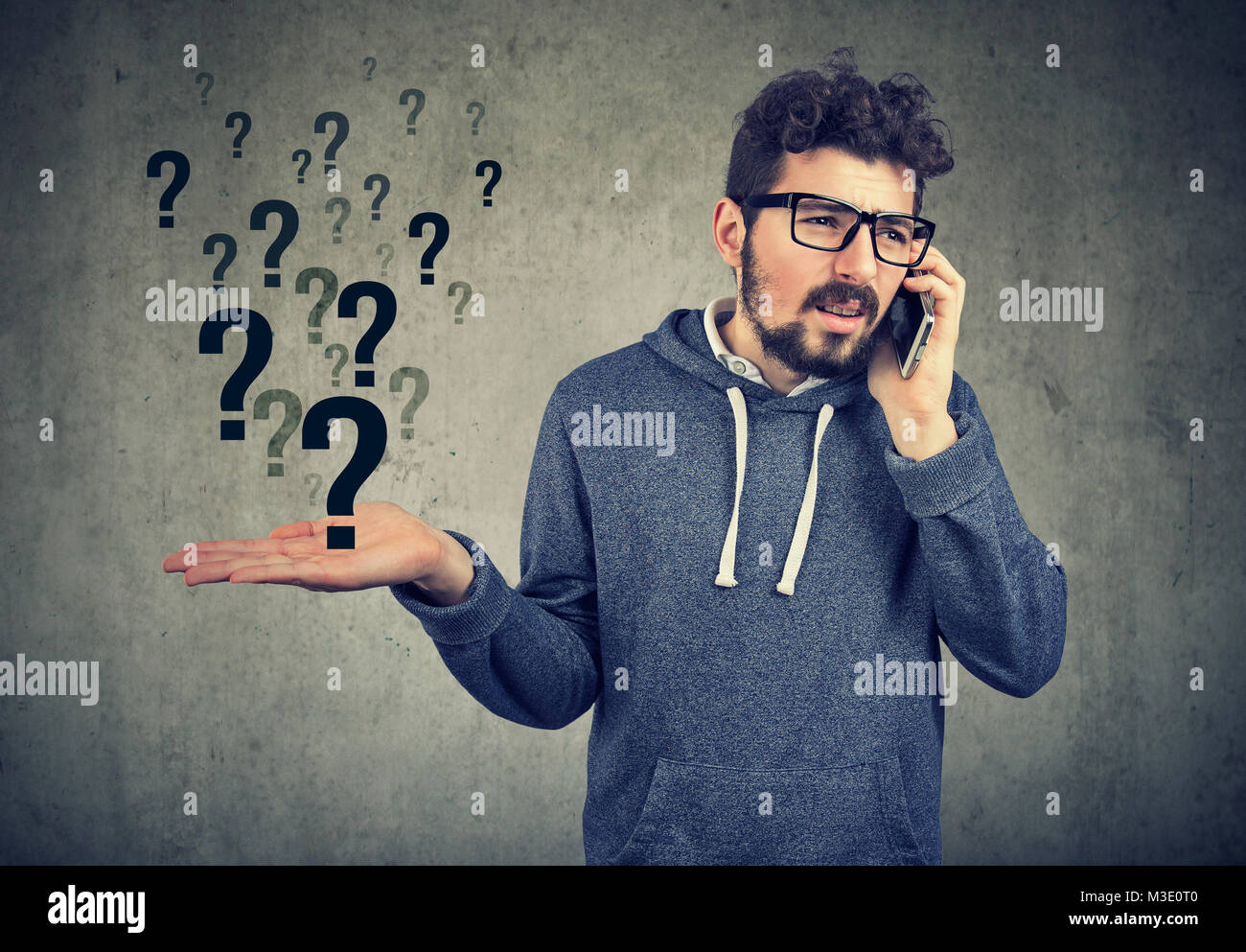 Young bearded man talking on smartphone in misunderstanding on gray background. - Stock Image