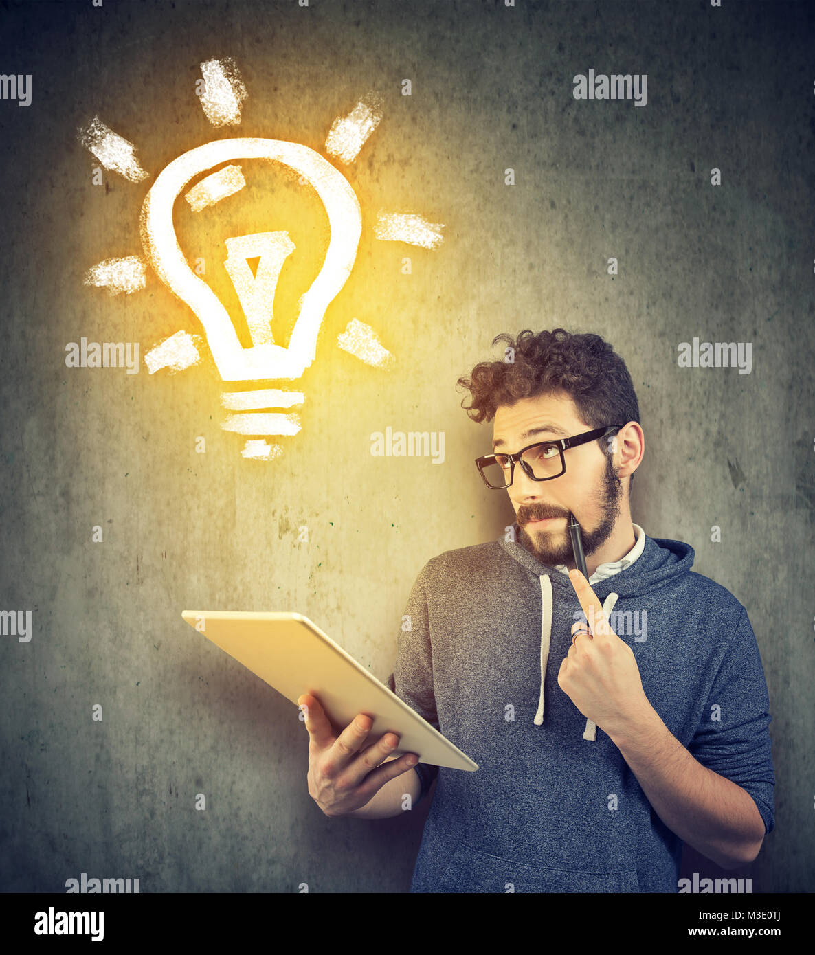 Casual young student using tablet and creating new idea looking up. - Stock Image