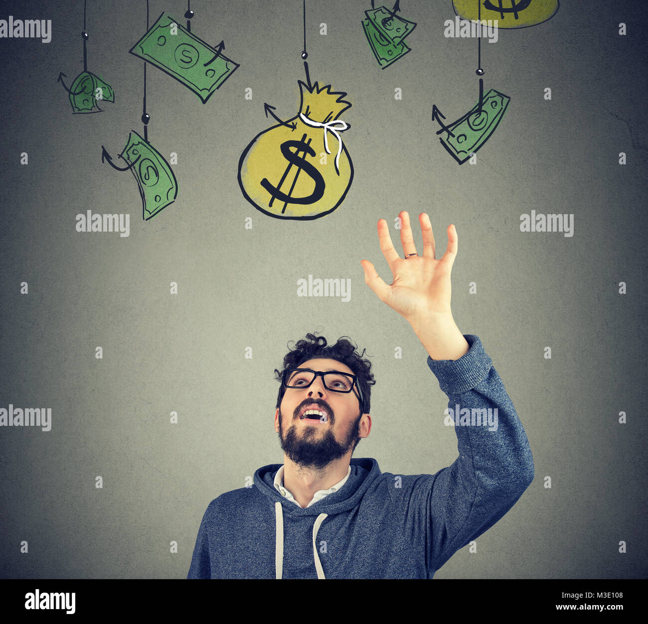 Hipster handsome man trying to grab a sack of money with his hand - Stock Image