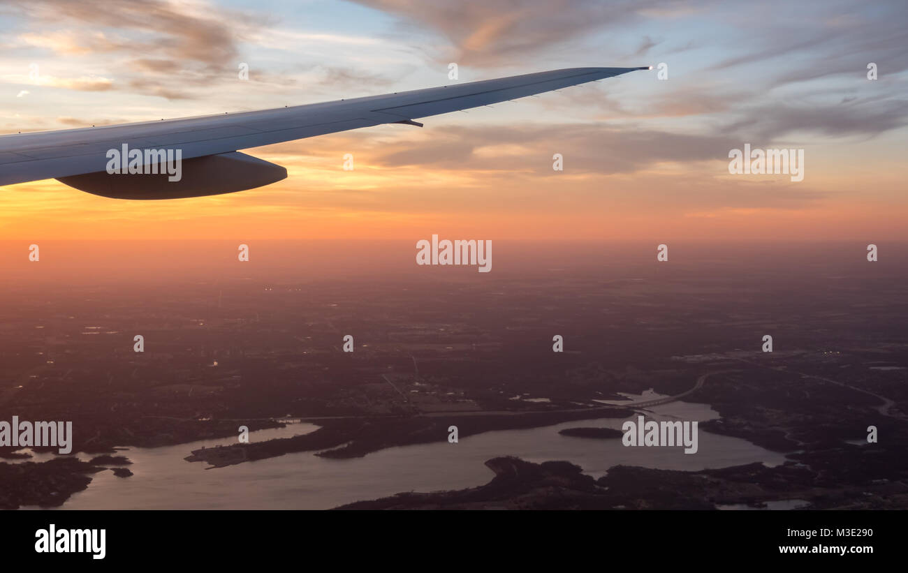 Orange Skies and Airplane Wing with Lake and City in the Background - Stock Image