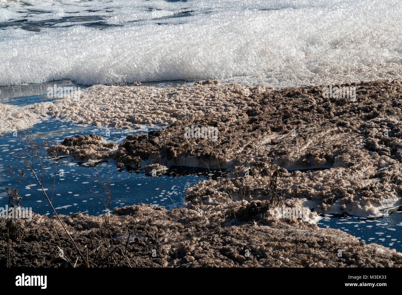 River pollution. Foam in Tejo (Tagus) River from high organic matter content on the water and toxic chemical pollution. - Stock Image