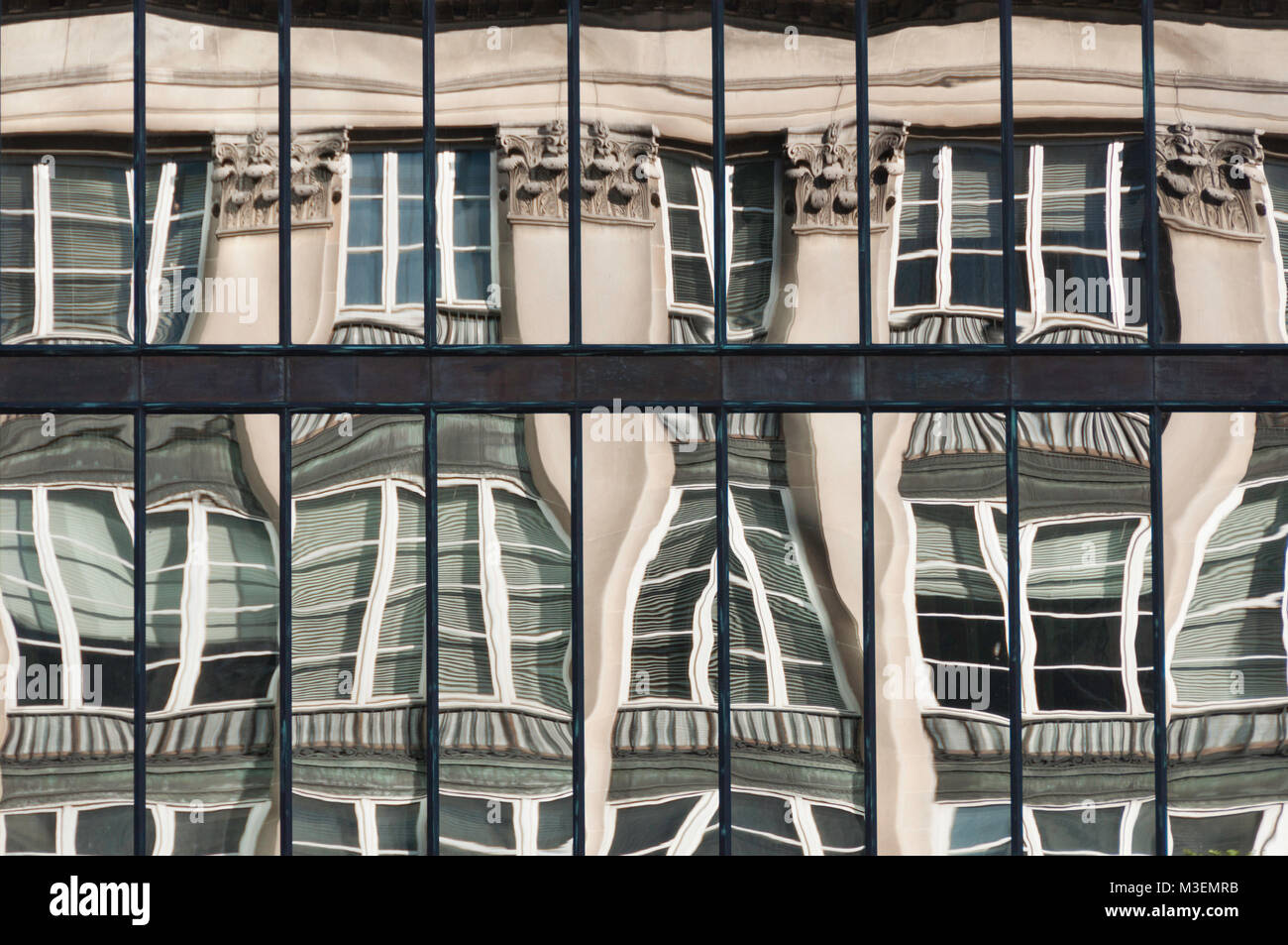 warped reflection of old building in windows of new glass front modern building - Stock Image