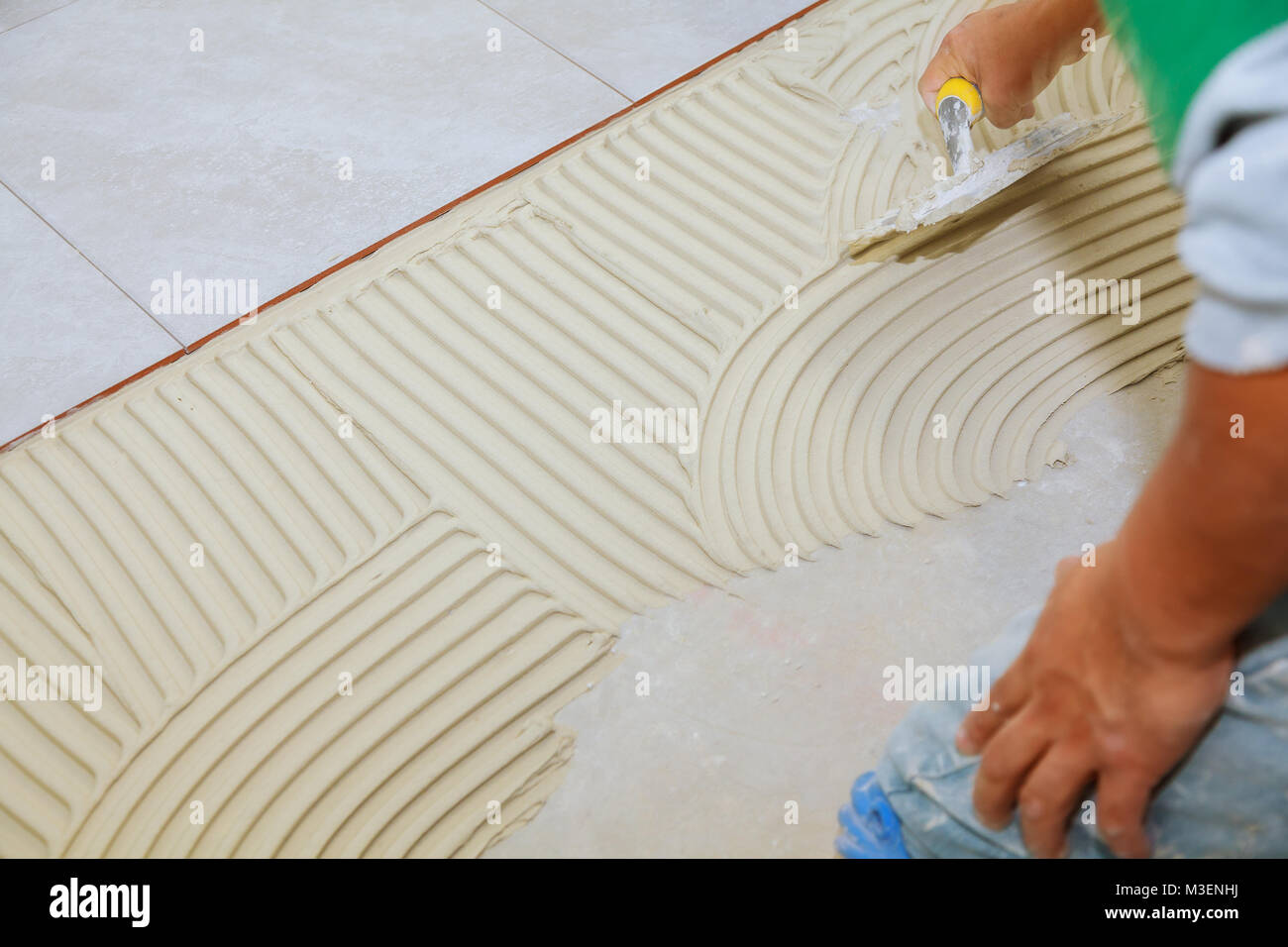 Master puts adhesive Spreading wet mortar before applying tiles on ...