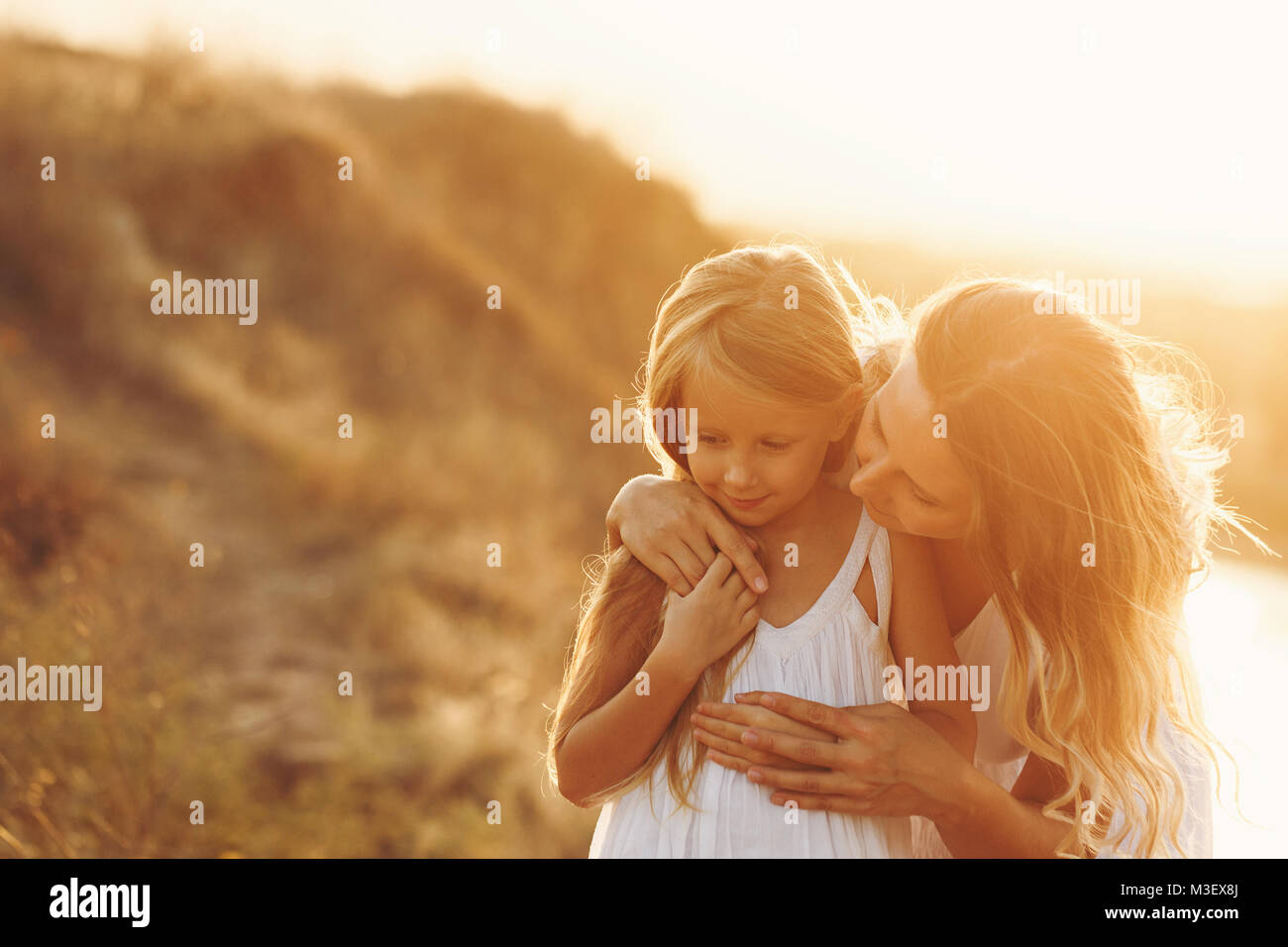 Family, mother and daughter on the river bank. The girl bends over and says something to her daughter. Girls in - Stock Image