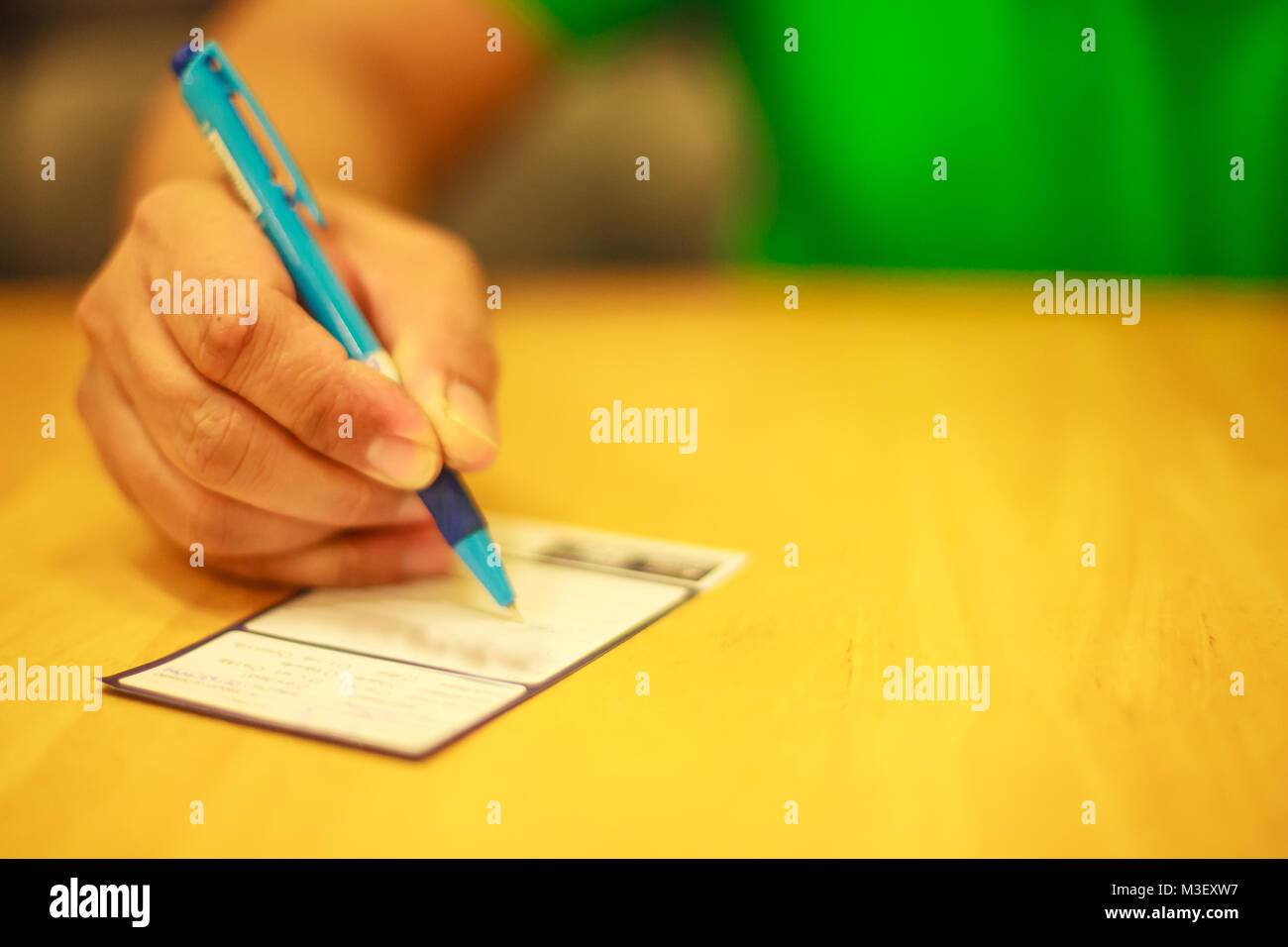 Man's right hand writing on the lucky draw coupon, memo, comment, suggestion or questionnaires on the wooden - Stock Image