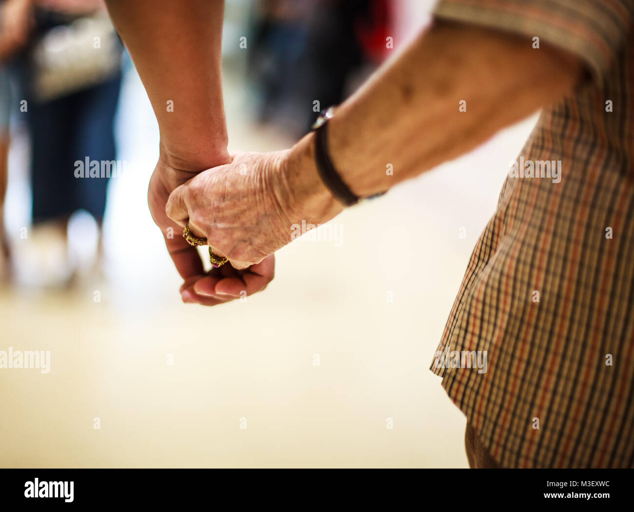 wrinkled elderly woman's hand holding to young man's hand, walking in shopping mall. Family Relation, Health, - Stock Image