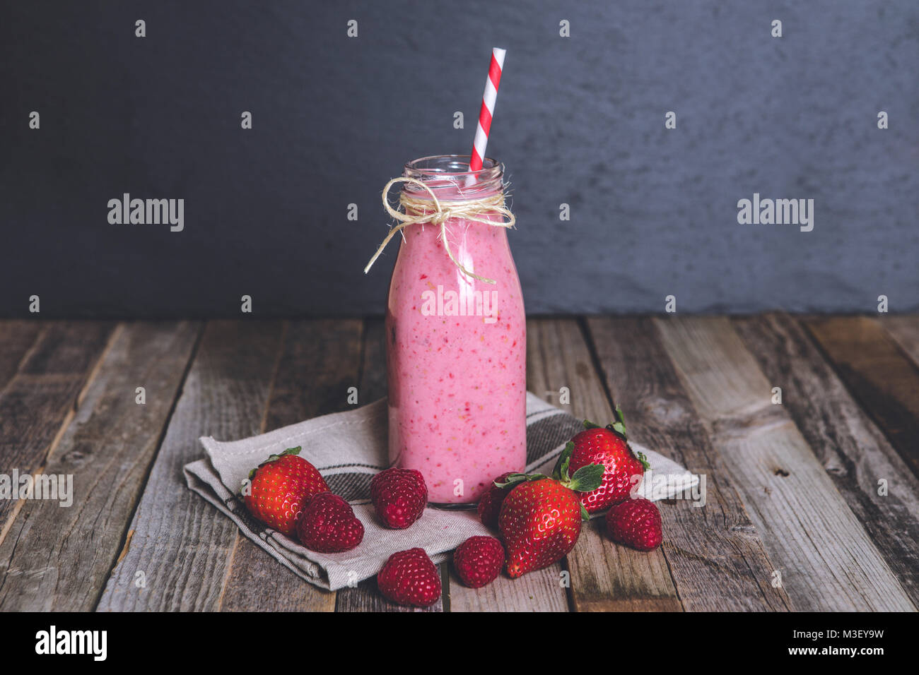 Glass of delicious berry smoothie on wooden background. Tabletop, front view. - Stock Image