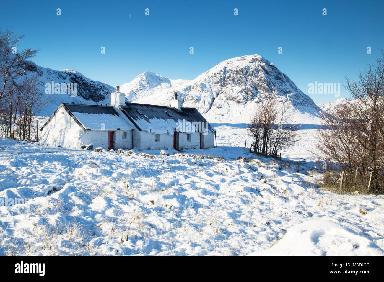 Black Rock Cottage, at the foot of the Glencoe Ski Resort with Buachaille Etve Mor in the background. - Stock Image