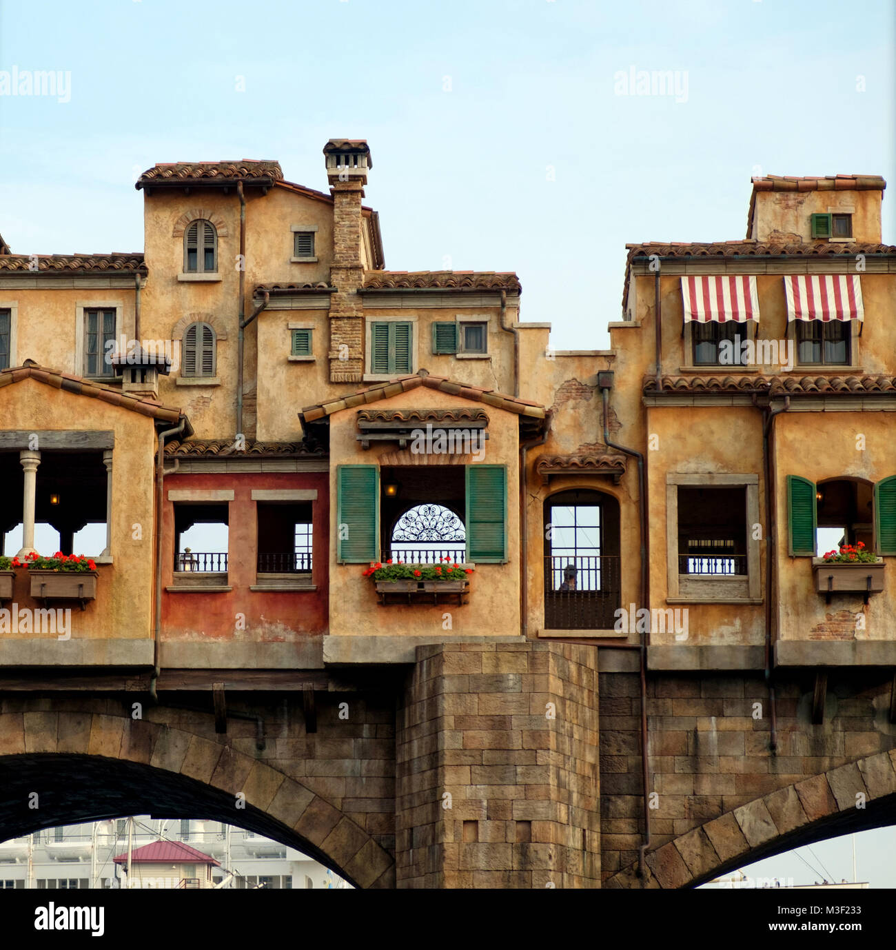 Italian style architecture. Weathered pale orange buildings with terracotta tiled roofs, red & white striped - Stock Image