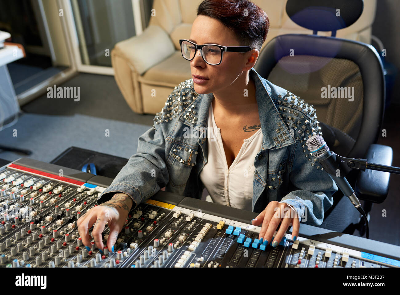 Pensive sound director using audio mixer in studio - Stock Image