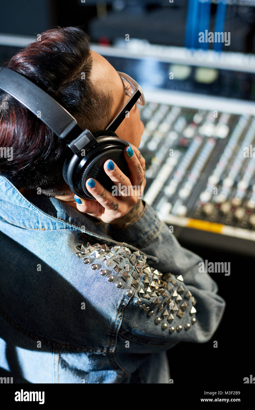 Producer listening to audio track in studio - Stock Image
