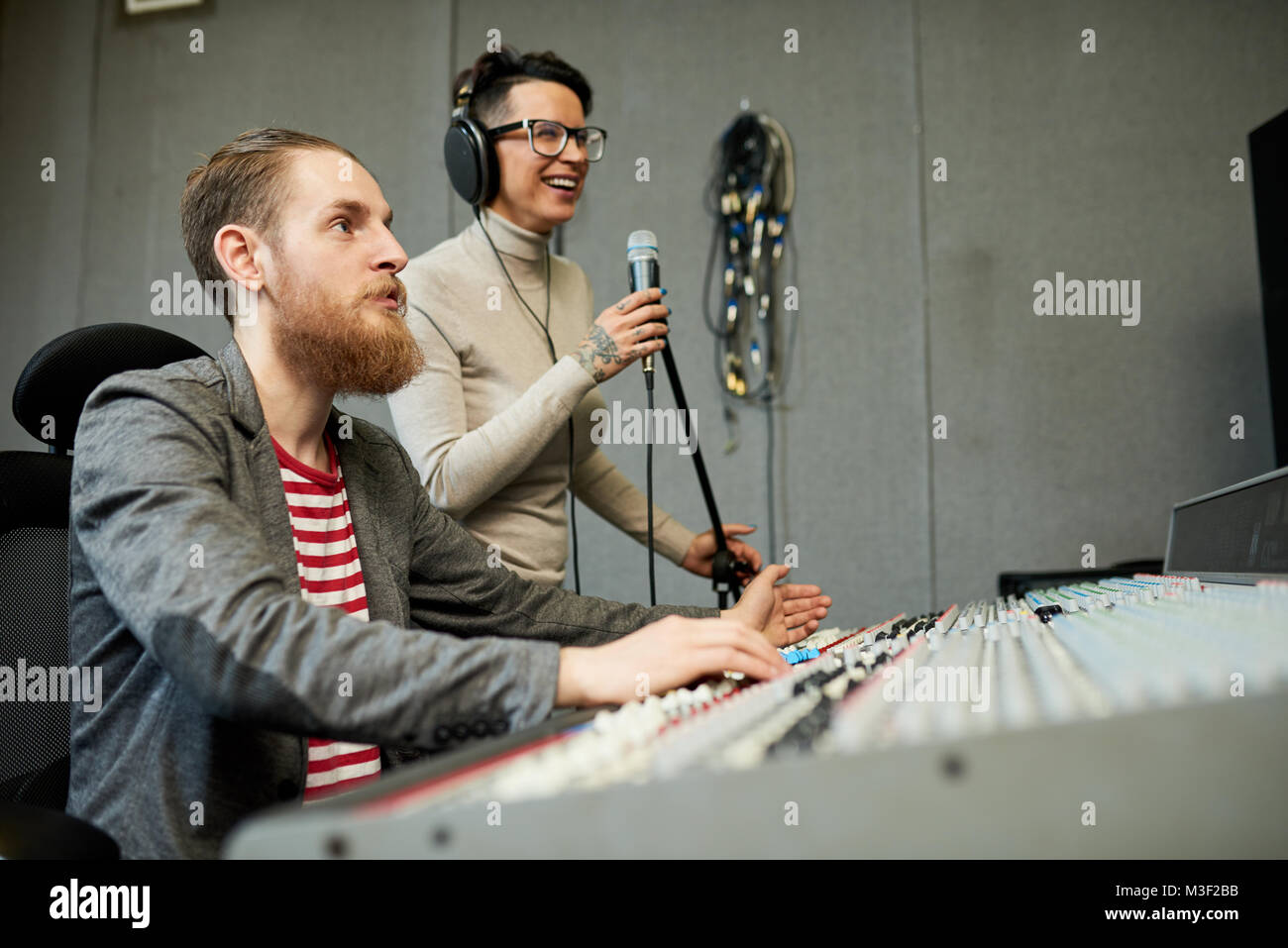 Sound designer and singer recording song in production studio Stock Photo