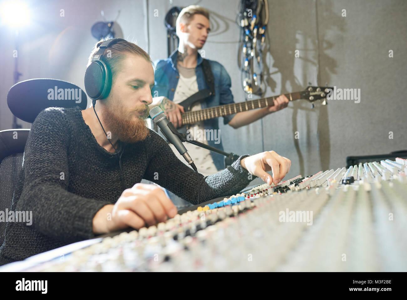 Sound engineer recording guitar performance in studio Stock Photo
