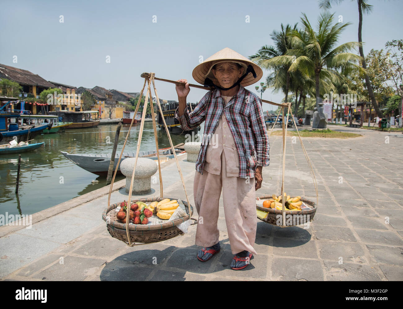 Traditional Vietnamese old lady carrying fruit in traditional baskets in ancient town of Hoi An  Vietnan. - Stock Image