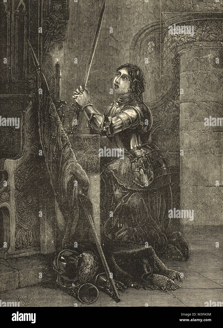 Joan of Arc in armour knelt in prayer - Stock Image