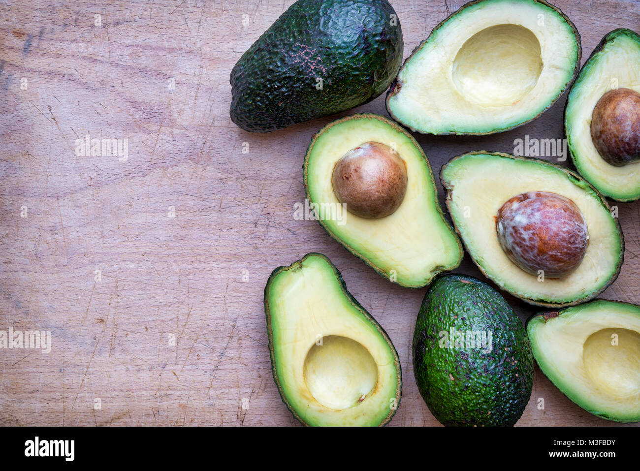 Persea americana. Avocado pattern on a wood background - Stock Image