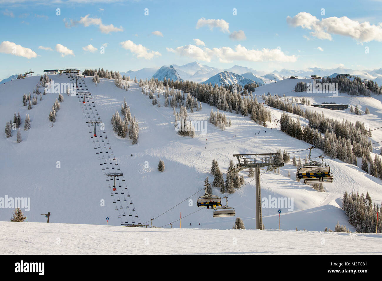 SCHEFFAU, AUSTRIA - JANUARY 18th, 2018: People enjoy the weather on the slopes in  ski resort of Scheffau, Austria. - Stock Image