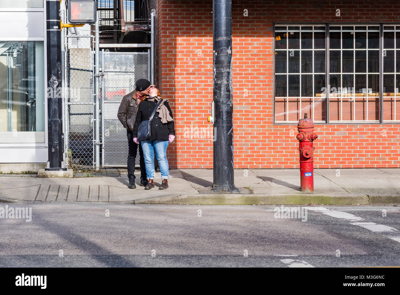PDA. a public display of affection. A kiss while waiting for the light to change. - Stock Image