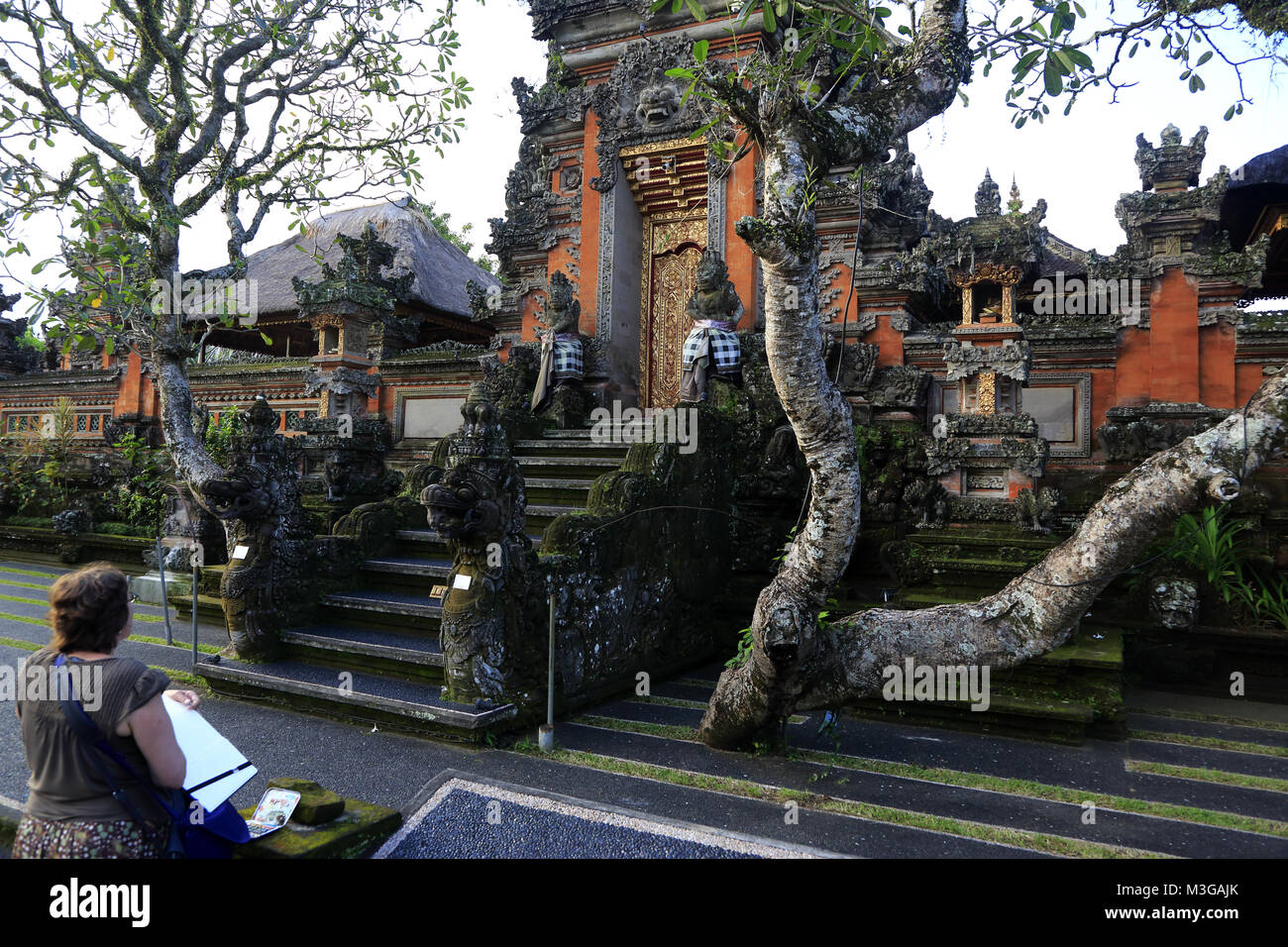 A tourist making sketch of the main entrance of Pura Taman Saraswati Temple.Ubud.Bali.Indonesia - Stock Image