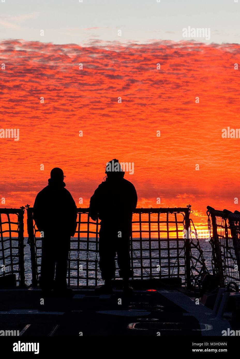 ATLANTIC OCEAN (Feb. 3, 2018) Yeoman 1st Class James Gray, left, and Yeoman 2nd Class Kobi Gaskin watch the sunset - Stock Image