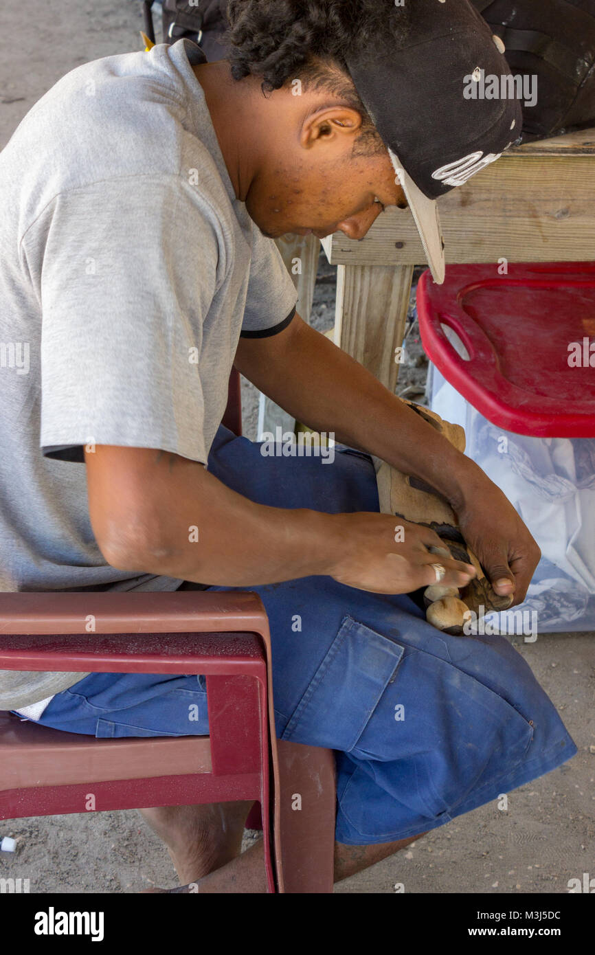 San Pedro, Ambergris Caye, Belize - January 19, 2018:  A local artisan works on a handmade piece.  Located at the - Stock Image