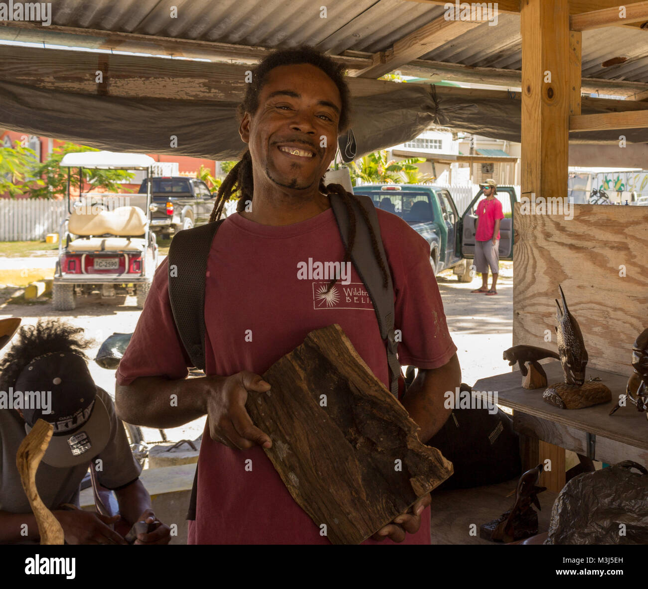 San Pedro, Ambergris Caye, Belize - January 27, 2018:  A local artisan displays a piece of wood that will soon become - Stock Image
