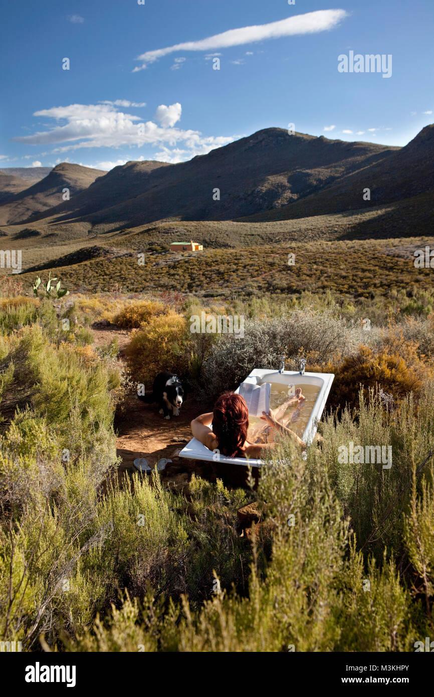 South Africa, Western Cape, Montagu, Simonskloof Mountain Retreat. Woman taking outdoor bath. - Stock Image