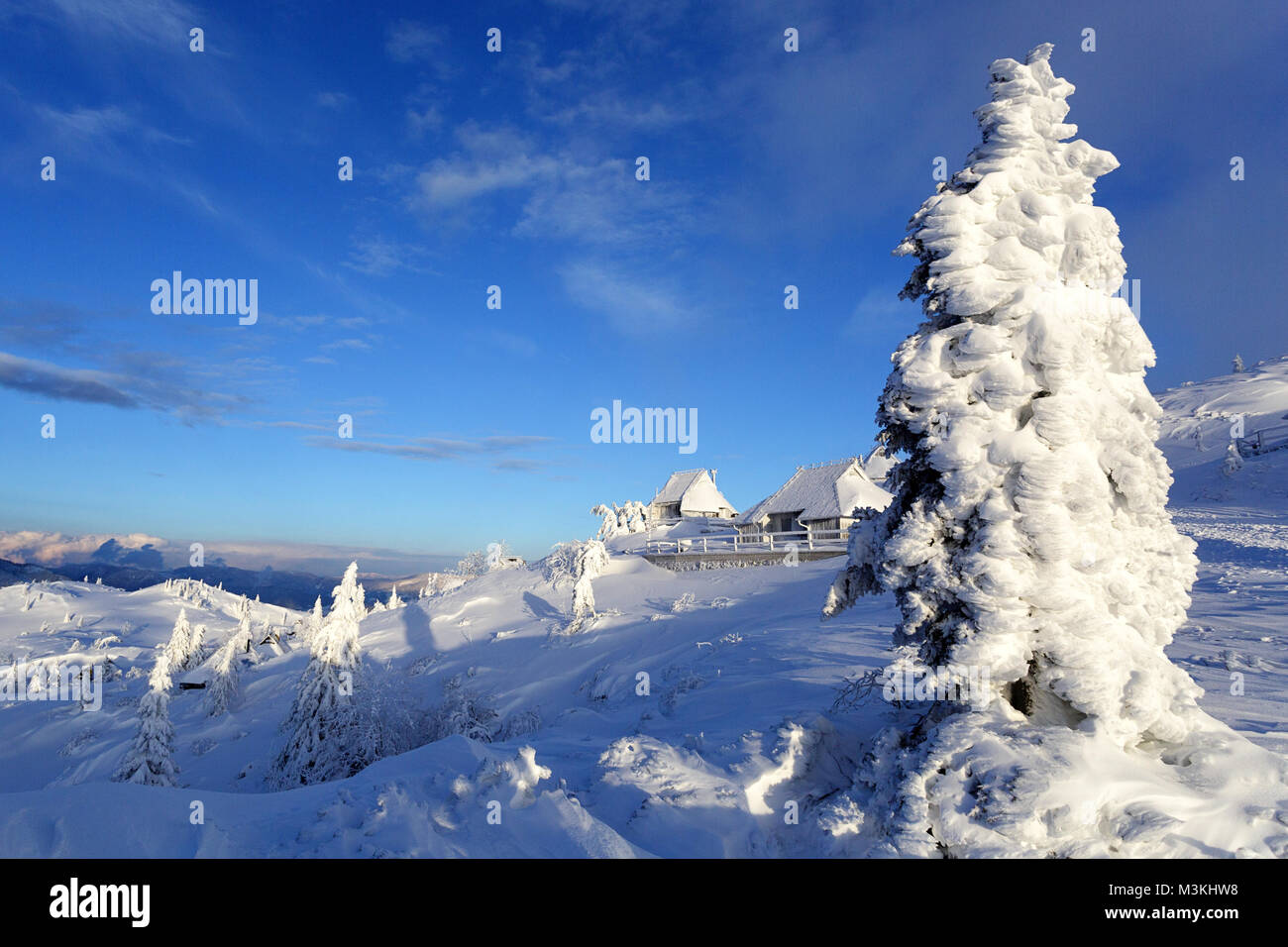 Winter scene on a snow covered mountain with frozen cabins and pine trees. Stock Photo
