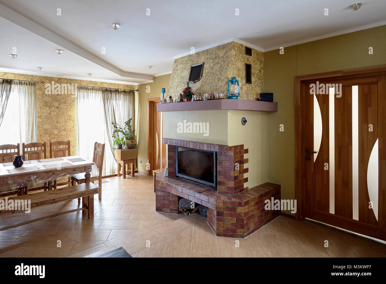 Fireplace and Table in Livingroom with Cups, Lamps and Christmas Tree on Mantelpiece - Stock Image