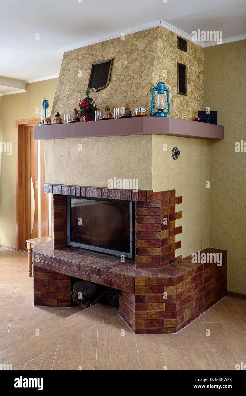 Fireplace in Livingroom with Cups, Lamps and Christmas Tree on Mantelpiece - Stock Image