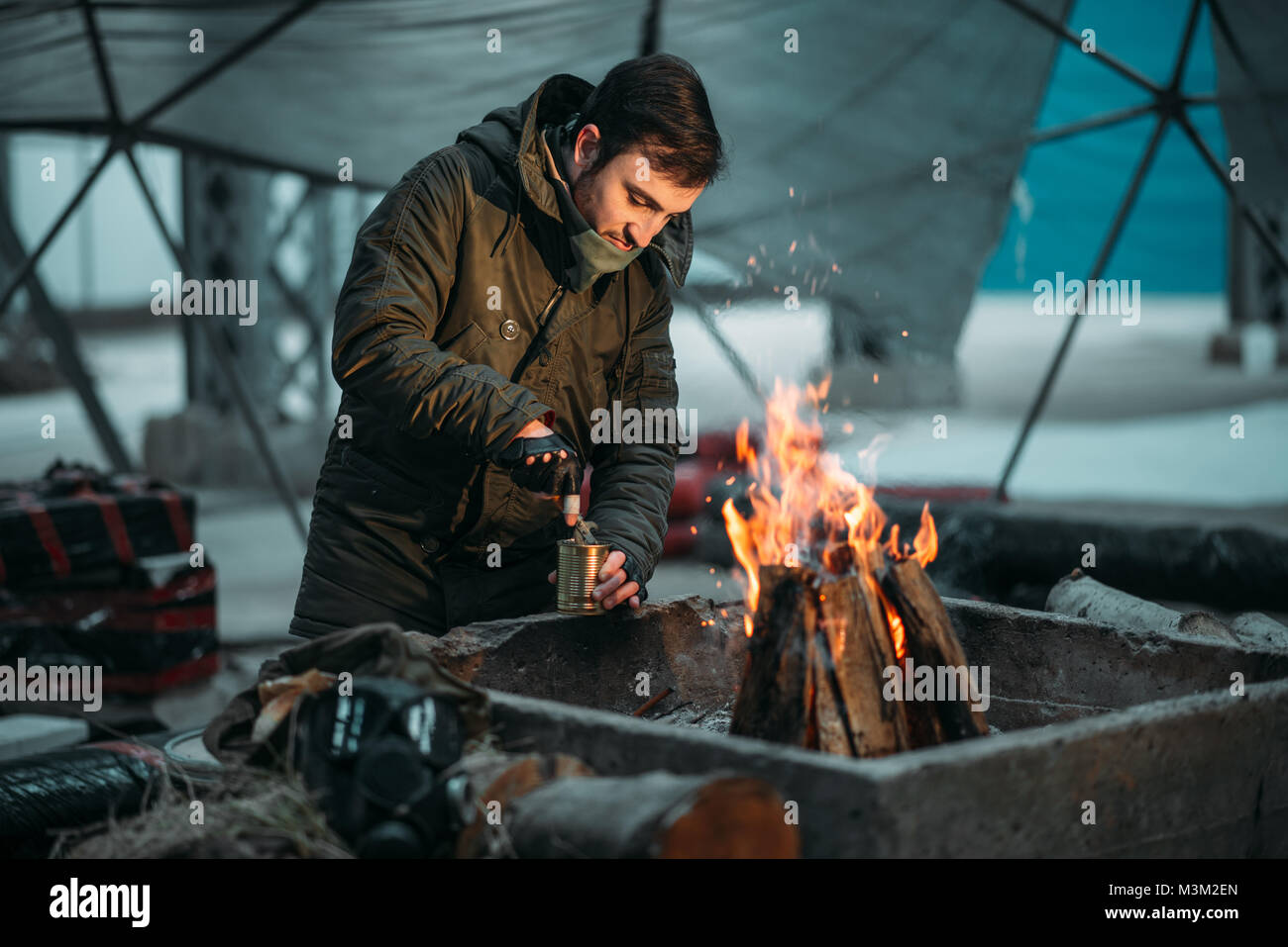 Stalker, male person cooking canned food on fire. Post apocalyptic lifestyle, doomsday - Stock Image